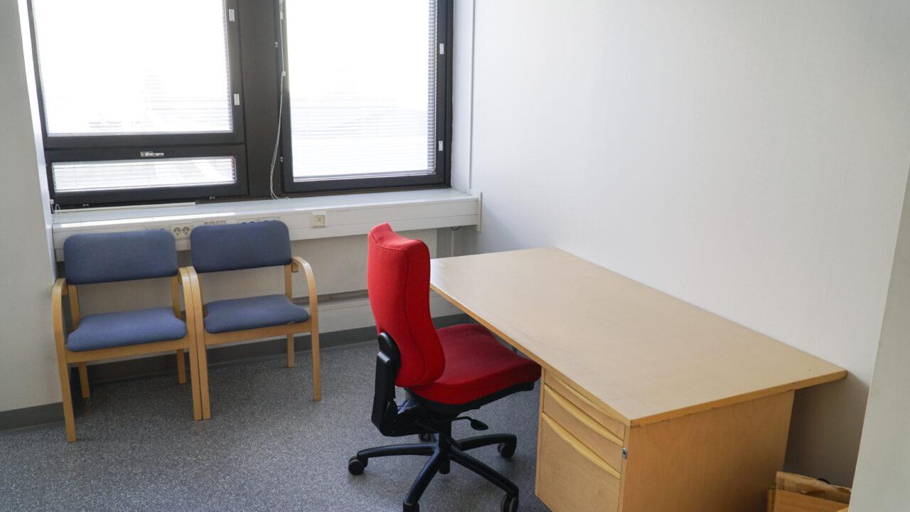 Hyvä työympäristö. Tarjolla on vuokrattavia työhuoneita. Työpöytä ja työtuoli työhuoneessa ikkunoiden vieressä.