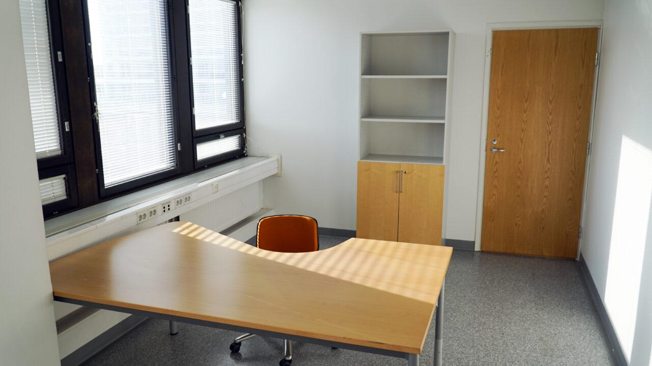 Vuokrattava työhuone voi olla hyvä työympäristö esimerkiksi asiantuntijatyön tekemistä varten. Puinen muotoiltu työpöytä, oranssi työtuoli, kirjahylly ja lukollinen kaapisto tavaroille. Työpöydän vieressä ikkunat, joissa sälekaihtimet auki. Aurinko paistaa huoneeseen.