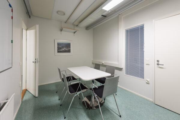 Liikehuoneiston vuokrasopimus. Taukohuone, vaaleat seinät, kaksi ovea. Keskellä huonetta on pieni pöytä ja viisi tuolia. Vaaleanvihreä lattia.