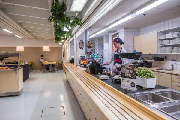 Liikehuoneiston vuokrasopimus tekeillä? Haukiputaan Teollisuustiellä sijaitseva henkilöstöravintolan asiakaspalvelupiste, jossa ravintolayrityksen henkilö työskentelee maksupäätteellä.