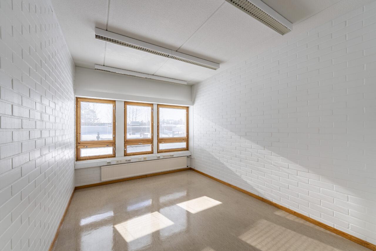 Yksi kiinteistön (Toritalo) työhuoneista. Huoneen päässä on kolme ikkunaa, joista paistaa aurinko. Vaaleanruskea kiillotettu lattia. Valkoiset tiiliseinät. Katossa valaisimia. Huoneen koko on yli 10 neliömetriä.