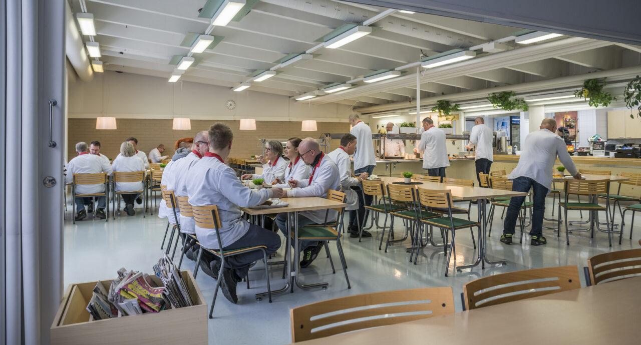 Lounasravintola (Teollisuustie Haukiputaalla), missä ihmisiä ruokailemassa. Osa istuu tiimin kesken pöydän äärellä, osa on linjastolla valitsemalla lounasta.