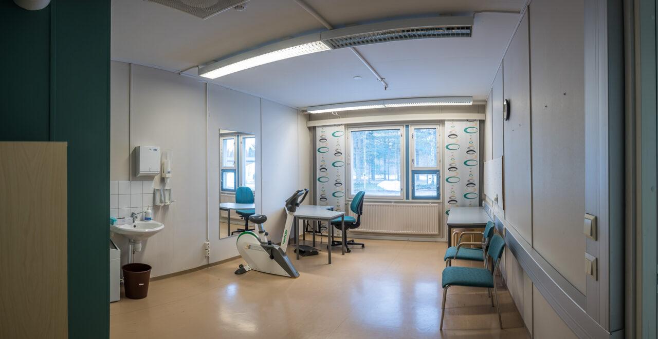 Toimitilaa (Teollisuustie, Haukipudas), jossa on ollut työterveys- ja hyvinvointipalveluita tarjoava yritys. Käsienpesupiste, kuntopyötä, työpiste, tuoleja vaaleat seinäpinnat ja paneeliverhot.