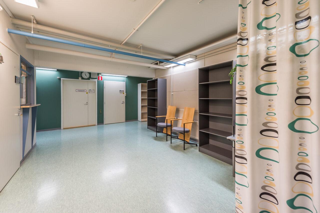 Esimerkki asiakkaiden odotustilasta/huoneesta. Toimitilassa väliverhot, kirja- ja lehtihyllyjä ja asiakastuoleja sekä vastaanottohuoneita, joiden ovat ovat kiinni. Suurikokoinen seinäkello. Toimitilan sijainti: Teollisuustie, Haukipudas.