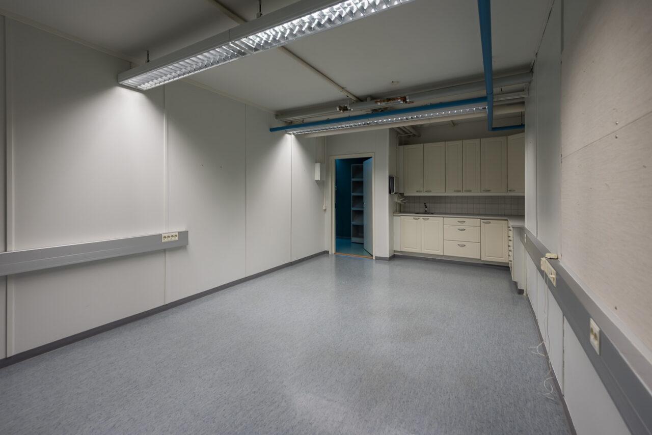 Tyhjä ja vuokrattavana olevan toimitilan yksittäinen huone (Teollisuustie, Haukipudas), jossa siniharmaa lattiapinta ja vaaleat seinät. Huoneessa on myös keittiönurkkaus, jossa on työtaso. Vaaleat kaapistot.
