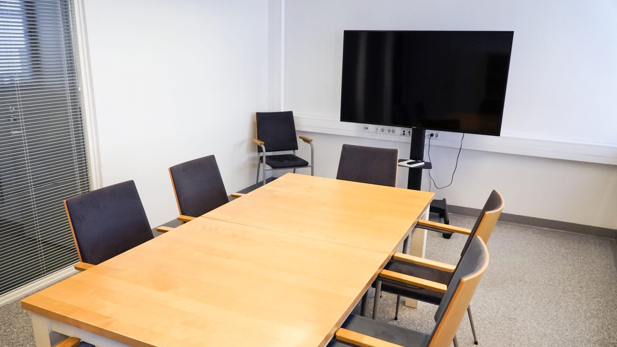 Hyvä työympäristö on monelle tärkeä asia. Esimerkkinä neuvotteluhuone, missä on puupintainen lakattu neuvottelupöytä. Kankaalla pehmustettuja työtuoleja. Älytelevisio asennettuna liikuteltavalle lattiajalustalle.