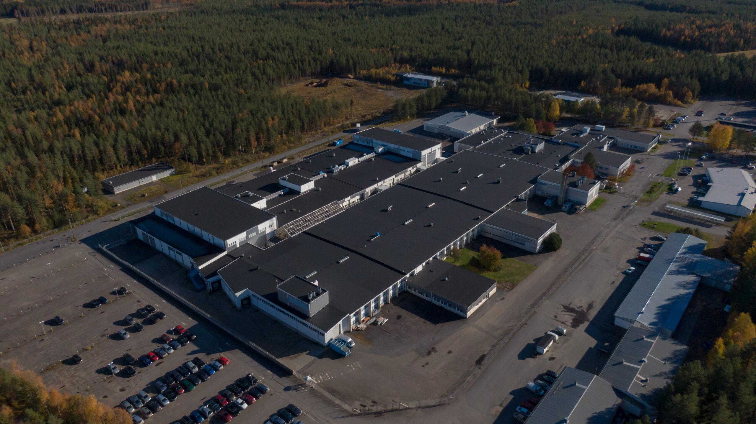 Ilmakuva teollisuusalueelta (Teollisuustie). Suuri toimitilakiinteistö kuvan keskellä. Autoja pysäköintialueella.