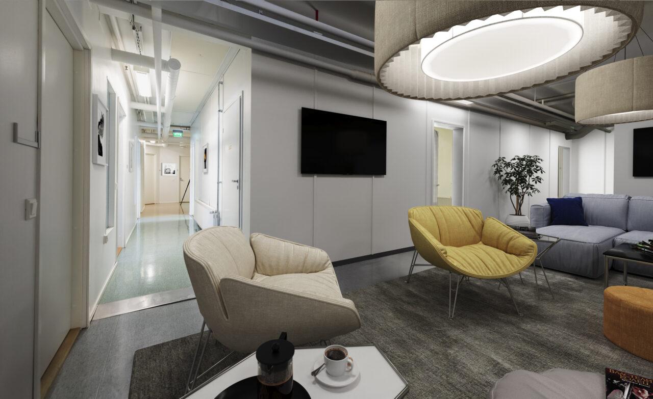 Hybiridityö ja siihen soveltuva toimitila. Aula- tai asiakastila yrityksen toimistossa. Harmaa sohva, nojatuoleja, pöytiä ja älytelevisio.