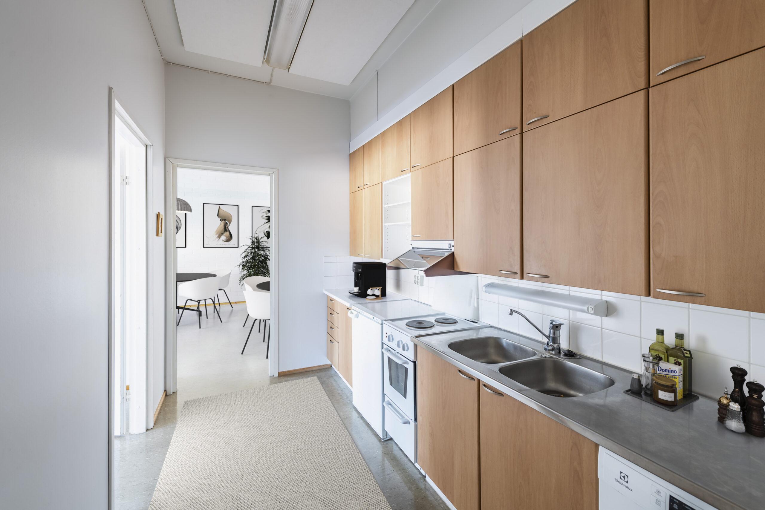 Turvallinen työympäristö tarkoittaa esimerkiksi keittiötä, jossa on turvalliset ja asianmukaiset laiteratkaisut. Toimitilan keittiö, jossa runsaasti työtasoa. Kahvinkeitin, jääkaappi, pienehkö sähköliesi, kaksi tiskiallasta, vesihana ja astianpesukone. Pöydällä muun muassa maustepurkkeja.