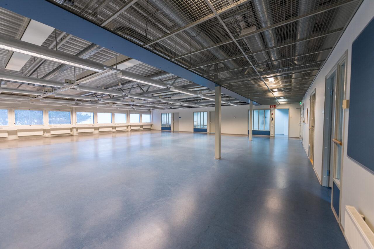 Verkkokaupan perustaminen voi vaatia myös toimitiloilta neliöitä. Varsinkin, jos yritystoiminta kasvaa vähänkin merkittävämpään kokoluokkaan. Toimitila, jossa on runsaasti neliöitä. Sininen lattia, paljon ikkunoita sekä teräsrakenteita ja valaisimia katossa.